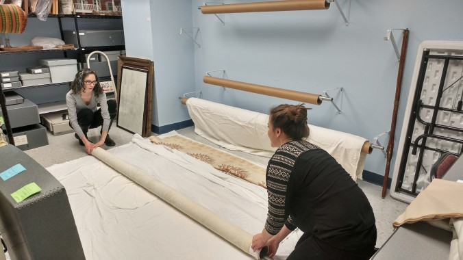 Hannah helps Curator Mary Beth with piece from our textile collection.